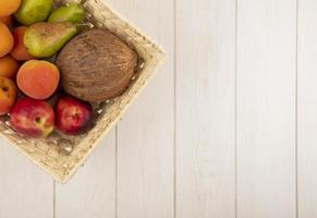 Surtido de frutas en una canasta sobre fondo neutro