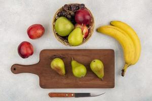 Assorted fruit on cutting board on neutral background