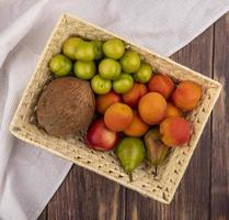 Fruit in a basket with cloth on wooden background