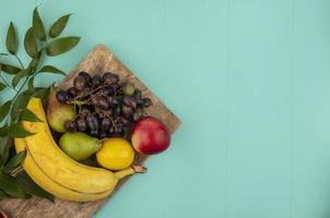 Fruta variada sobre fondo azul con espacio de copia