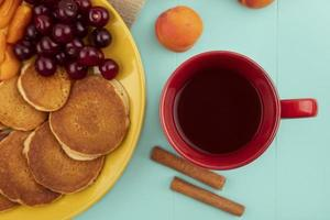 Cup of tea with pancakes on blue background