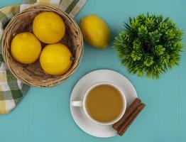 Taza de té con limones sobre fondo azul.