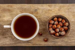 Cup of tea with nuts on wooden cutting board
