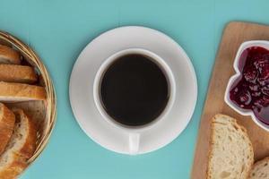 Taza de té con pan y mermelada sobre fondo azul. foto