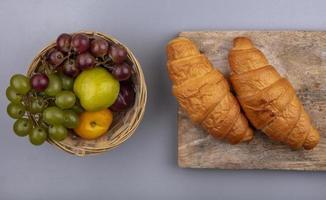 Surtido de frutas y pan sobre fondo neutro