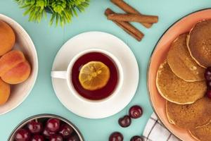 Cup of tea with pancakes and fruit on blue background
