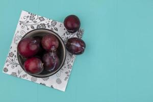 King pluots in a bowl on blue background with copy space