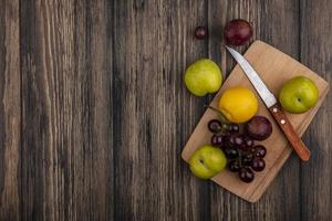Assorted fruit on cutting board on wooden background