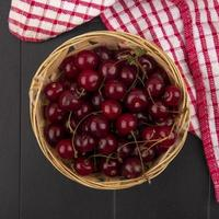Top view of cherries in a basket on plaid cloth