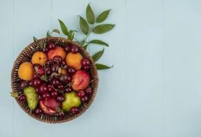 Basket of fruit on blue background with copy space photo