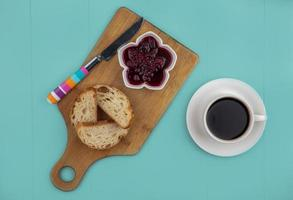 Bread with jam and coffee on blue background