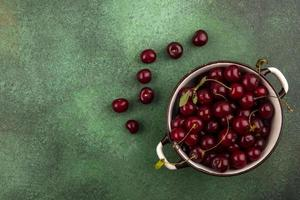 Cherries in a bowl on green background with copy space photo