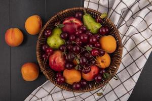 Vista superior de la fruta en una canasta sobre tela escocesa