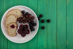 Toast with jam and fruit on green background photo