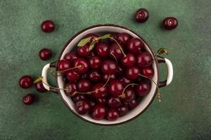 Cherries in a bowl on green background