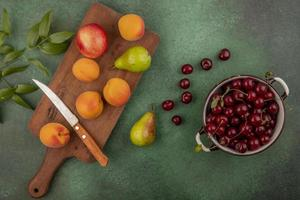 Assorted fruit on green background photo