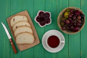 Té con frutas y tostadas sobre fondo verde de madera foto