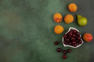 Fruta variada sobre fondo verde con espacio de copia