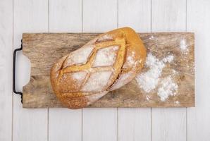 Vista superior del pan crujiente en la tabla de cortar foto
