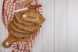 Rebanadas de pan sobre fondo de madera de tela escocesa con espacio de copia foto