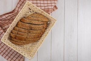 Fresh bread on plaid cloth on wooden background with copy space photo