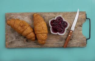 Croissants and raspberry jam with knife on cutting board on blue background