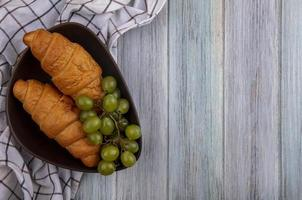 Croissants and grapes with plaid cloth on wooden background photo