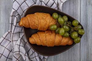 Croissants y uvas con tela escocesa sobre fondo de madera