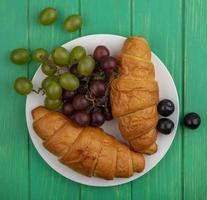 Croissants and grape in plate on green background photo