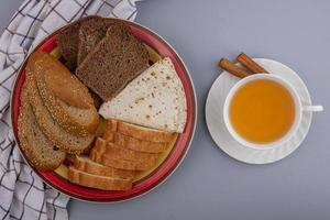 Assorted bread with tea on neutral background