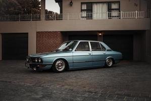 Cape Town, South Africa, 2020 - Blue sedan parked beside house