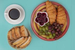 Juego de desayuno de pan y fruta con una taza de té sobre fondo azul.