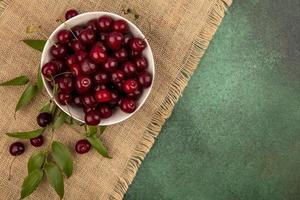 Cherries in a bowl ob sackcloth on green background photo