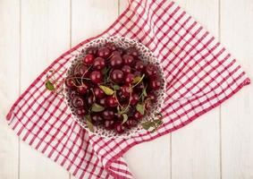 Bowl of cherries on plaid cloth and wooden background photo