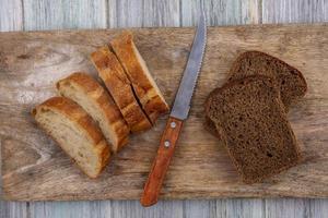 Pan surtido y cuchillo sobre fondo de madera foto