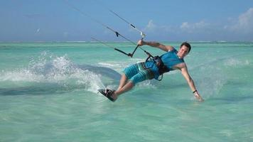 SLOW MOTION: Young surfer man kitesurfing in beautiful turquoise ocean lagoon