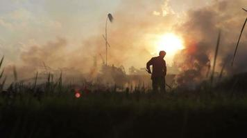 Silhouettes of farmer working and woman passing by in the smoke of stubble burning rice fields in Ubud Bali video