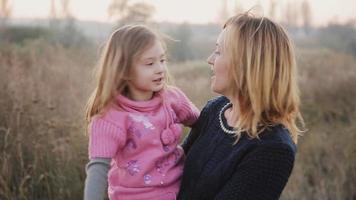 madre e hija en la naturaleza se ríen y se besan