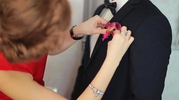 la ragazza appunta il fiore all'occhiello per lo sposo