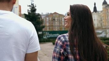 Attractive young man in white t-shirt and brunette woman on romantic date, walking holding hands, talking and happy smiling, looking at each other, back view