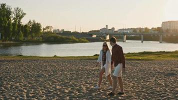 jovem casal caminhando na praia