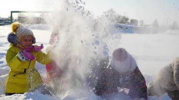 fröhliche Kinder, die im Schnee spielen, der Schnee im Park wirft
