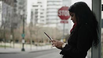 A young woman plays with her tablet as she wait for her bus