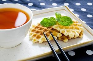 Tea with waffle and chopsticks in ceramic plate