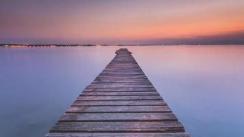 Muelle de madera largo en el lago de Garda al atardecer