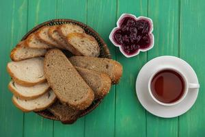 Sliced bread with cup of tea on green background