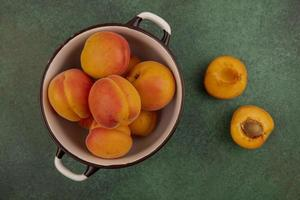 Apricots in a bowl on green background