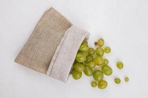 Bayas de uva blanca derramándose del saco sobre fondo blanco.