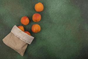 Apricots spilling out of sack on green background