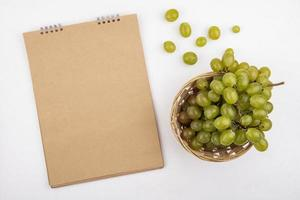 Grapes and a blank note pad on white background with copy space
